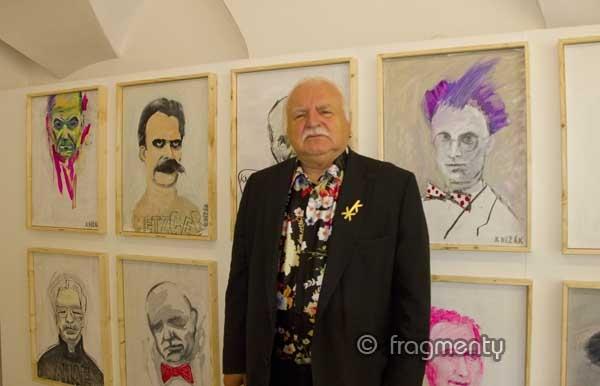 profesor MIlan Knížák před portréty návštěvníků svého ateliéru